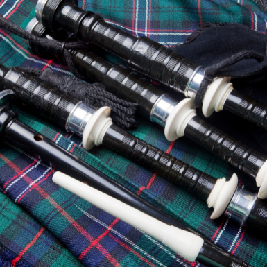 A set of bagpipes sitting on top of a tartan kilt