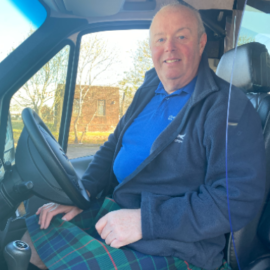 Tour Leader Cliff sitting in the drivers seat of the mini coach