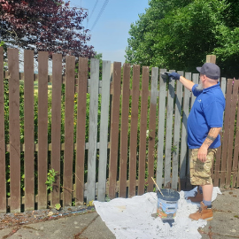 Tour Leader John painting the fence at the hospice