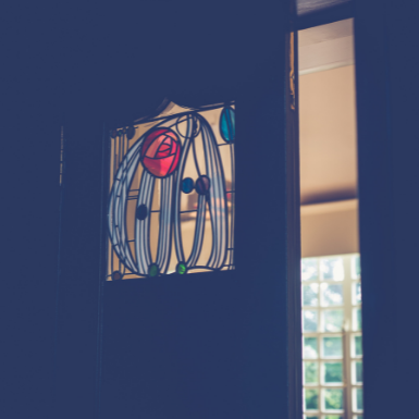 A stained glass window displaying Mackintosh's famous rose design within an interior door.