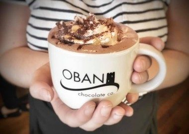 An Oban chocolate company mug containing hot chocolate & cream held in someone's hands