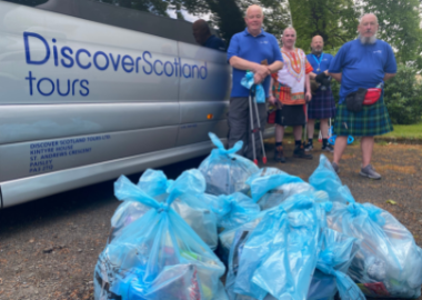 Our Tour Leaders Cliff, Michael, John & Stewart standing by the coach with the pile of bin bags that were collected.